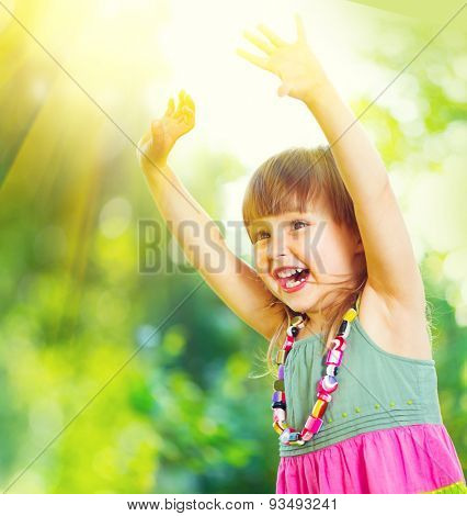 Happy Little Girl Having Fun outdoors. Beautiful Healthy three years old Child Laughing and raising hands, Playing and smiling in summer park.
