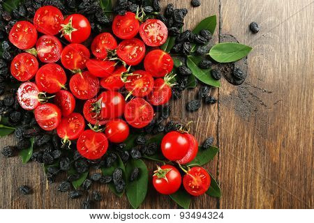 Cherry tomatoes with raisins arranged in heart shape on wooden background