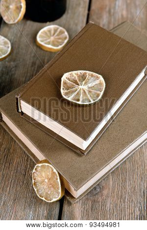 Old books with dry lemon on wooden background