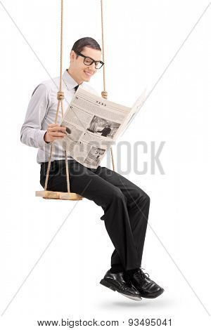 Vertical shot of a young cheerful man reading a newspaper seated on a swing . The photos used in the newspaper in my copyright, you can check from the Model release that I am uploading additionally.