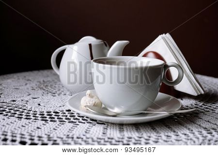 Hot chocolate in mug, on table, on dark background