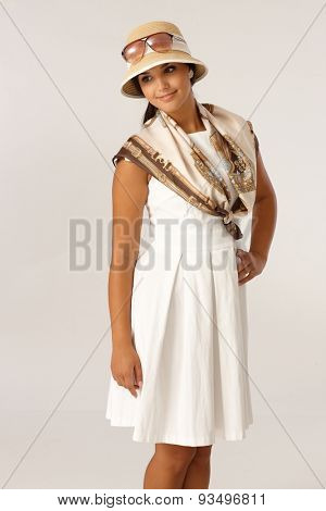 Pretty woman posing in summer dress and hat, smiling.