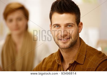 Closeup portrait of handsome young man. Woman at background.