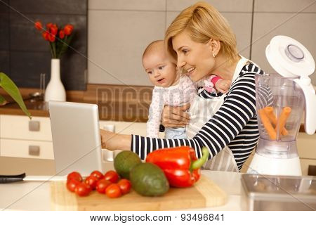 Mother and baby girl using laptop computer in kitchen, cooking.