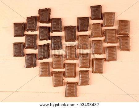 Chocolate pieces arranged in heart shape on light background