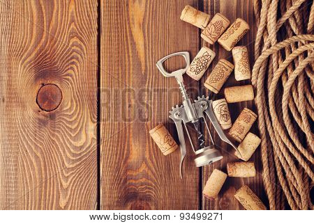 Wine corks and corkscrew over rustic wooden table background. Top view with copy space