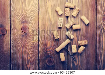 Wine corks and corkscrew over rustic wooden table background. View from above with copy space. Retro toned