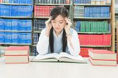 stock photo of pressure  - Young asian student under mental pressure in library - JPG