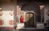 pic of rajasthani  - Woman in red scarf sitting near Lotus gate in City Palace of Jaipur Rajasthan India - JPG