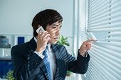 image of korean  - Korean manager talking on the phone and looking through blinds - JPG
