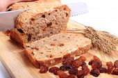 foto of fresh slice bread  - Slicing fresh baked wholemeal bread ears of wheat and heap of raisins lying on cutting board concept for healthy eating - JPG