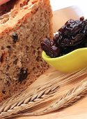 pic of fresh slice bread  - Slicing fresh baked wholemeal bread heap of dried plums and ears of wheat lying on cutting board concept for healthy eating - JPG