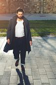 Постер, плакат: Young stylish man with black hair and beard walking down the street in stylish clothes