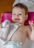 foto of diaper  - Closeup of adorable baby lying playing with a small white towel after the change of diaper - JPG