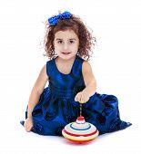 picture of dreidel  - Little girl spinning dreidel sitting on the floor - JPG