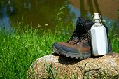 stock photo of canteen  - Hiking boots and a canteen on a rock in front of a pond - JPG