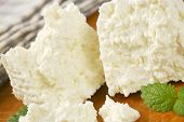 stock photo of curd  - detail of fresh curd cheese slices on wooden cutting board - JPG