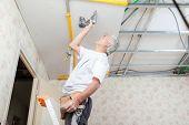 foto of suspenders  - Builder putting up a suspended ceiling - JPG