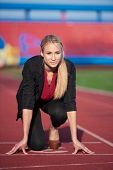 pic of race track  - business woman in start position ready to run and sprint on athletics racing track - JPG