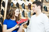 stock photo of shoe  - seller female assistant demonstrate shoes to young man during footwear shopping at shoe shop - JPG