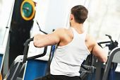 foto of triceps brachii  - athlete bodybuilder man doing back muscles exercises at weight machine in fitness sport club gym - JPG