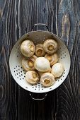 stock photo of champignons  - Fresh white champignons on dark wooden table - JPG