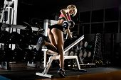 foto of muscle strain  - fitness girl execute exercise with dumbbells on broadest muscle of back - JPG