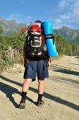 Tourist with a large backpack is a high mountain, poster
