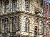 stock photo of scaffold  - Fragment of scaffolding against house wall in Prague