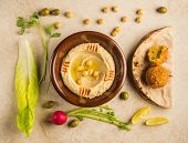 picture of dipping  - Various food ingredients arranged around bowl of Houmous  - JPG