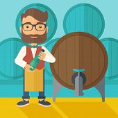 picture of inspection  - A wine maker standing wearing his apron holding a bottle of wine inspecting from barrel inside the wine storage room - JPG