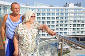 stock photo of vest  - Portrait of elderly man in striped vest with wife on the balcony - JPG