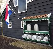picture of dairy barn  - barn with milk churns with a dutch flag - JPG