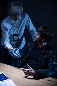 pic of interrogation  - Mature police officer interrogates a young man - JPG