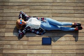 foto of jetties  - Attractive young woman enjoying sunshine while lying on the wooden pier with her tablet computer female carefree freelancer girl resting after work outside young female lying relaxed on a jetty - JPG