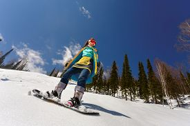 picture of snowboarding  - Snowboarder doing a toe side carve with deep blue sky in background - JPG