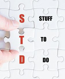 stock photo of std  - Hand of a business man completing the puzzle with the last missing piece - JPG