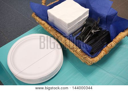 plastic plates, forks and napkins on the table for lunch in office