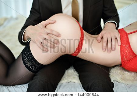 Young Sexy Couple On The Bed. Beautiful Lady And Guy In Erotic Pose. Portrait Of Girl And Boy Indoor