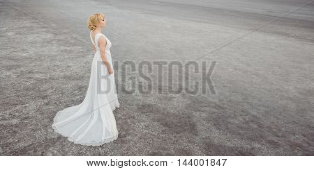 Bride outdoors in a desert looking afar. Beautiful woman in white dress full body length. Stretched wide photo. Gray background copy space good for texting. Some fine art noise.