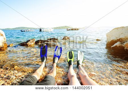 Snorkeler relaxing on a beach. Have a rest. Fins. Beach vacation snorkel. Relaxing on summer holidays lying down in water after snorkeling