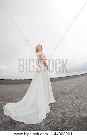 Bride outdoors in a desert looking afar. Beautiful woman in white dress full body length. Fish eye lens photo. Gray background copy space good for texting. Some fine art noise.