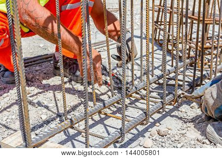 Workers are tying rebar to make a newly constructed footing frame. Binding concrete frame