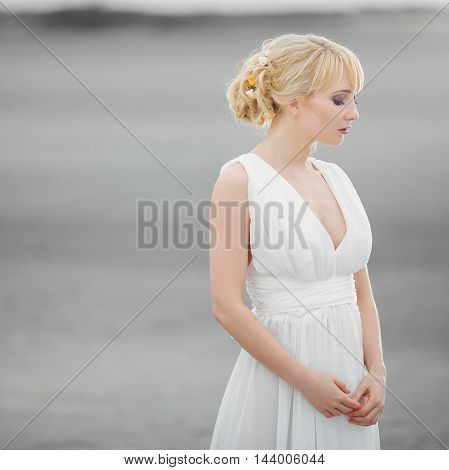 Portrait of beautiful elegant blond woman in white dress looking down. Gray background with copy space. Square picture format.