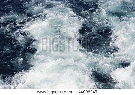 water wave splash after ship propeller in the sea