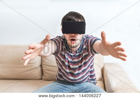 Young Man Is Fascinated From Virtual Reality Headset.