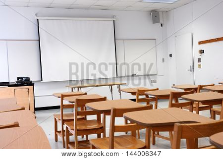 classroom with armed chairs and white board in university