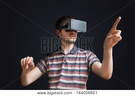 Young Man Is Wearing 3D Virtual Reality Headset And Touching Som