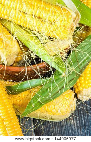 Fresh corn with leaves on a dark rustic wooden table, close view