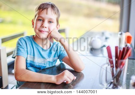 child in a cafe waiting for his order. cute boy sitting at a table and smiling, listening to his interlocutor. small talk in a restaurant awaiting food